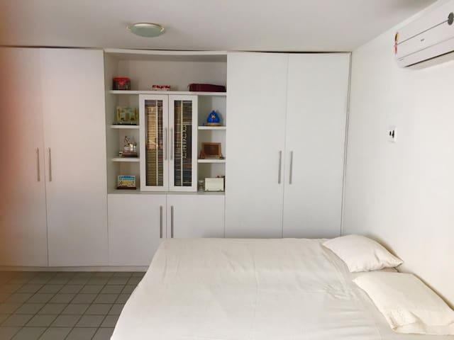 Quarto principal com ar condicionado e uma cama de casal