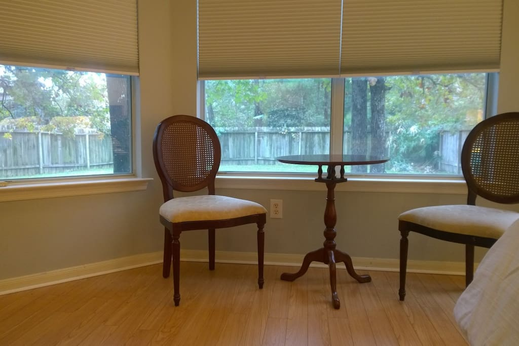 There is a bay window with a small sitting area in the room.