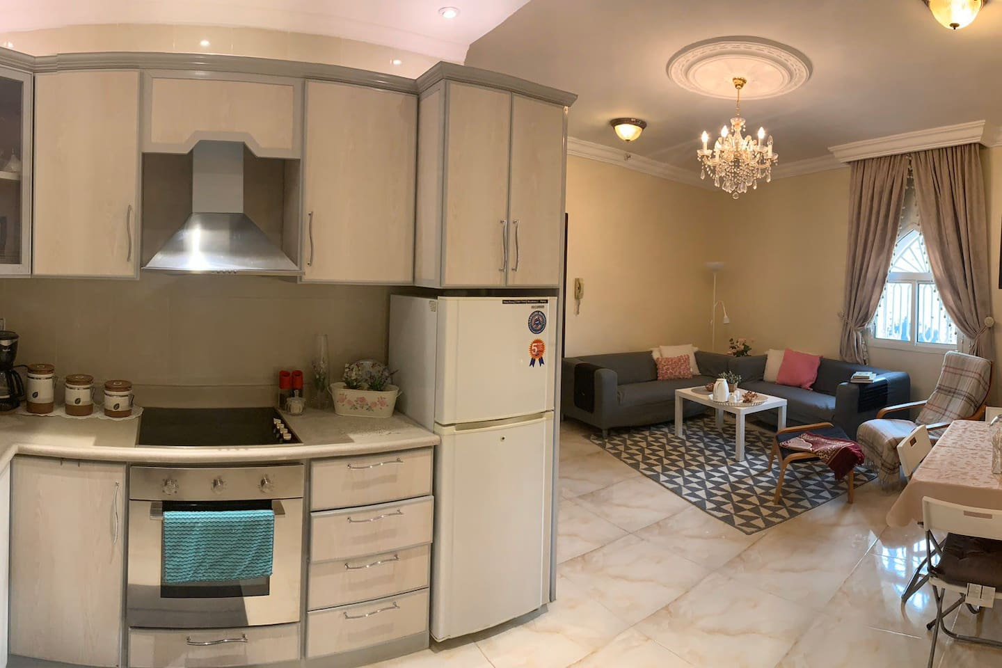 Panoramic view of the main living area showing the full kitchen, dining table, and living room