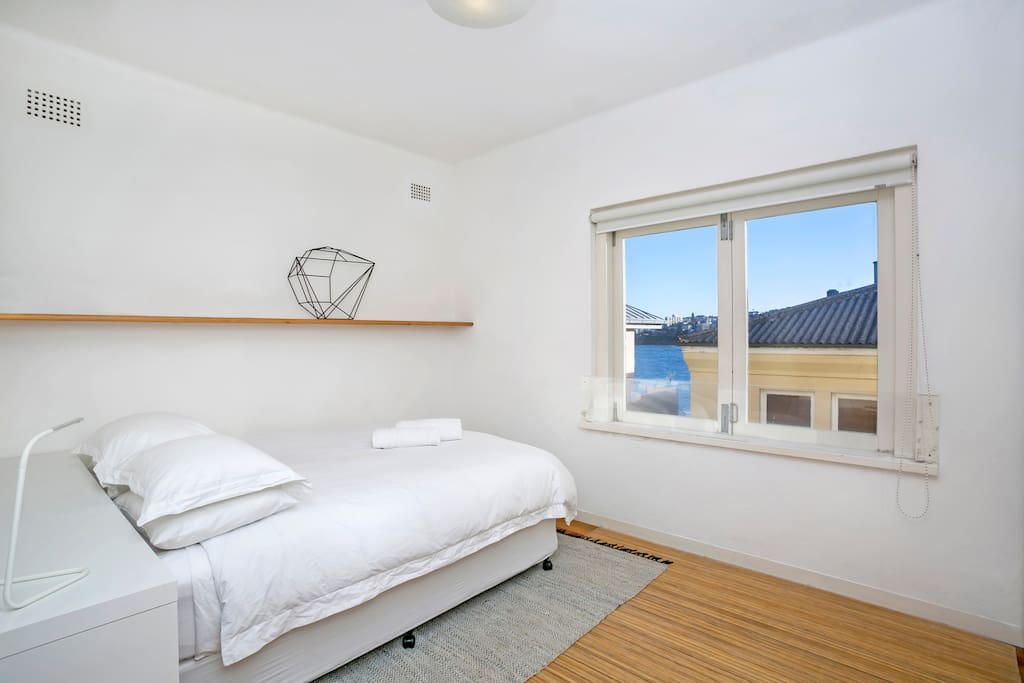 Sunny 1 bedroom with Queen size bed and ocean views. The window opens up fully, concertina style and the view looks down to the rocks, boat ramp and across the ocean.