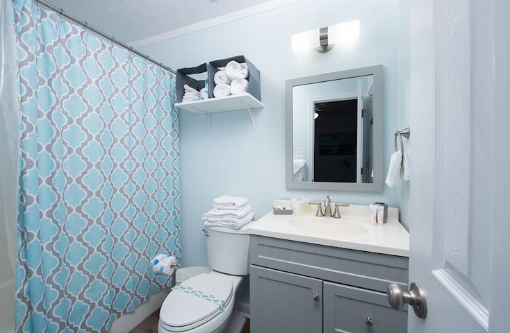 Bathroom with tub/shower combo. We are also proud to offer a hairdryer, Aussie shampoo and conditioner, and shampoo/conditioner/body wash combo for the kiddos!