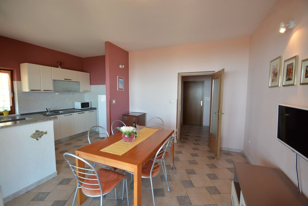 Kitchen with dinning table, and Tv place.
