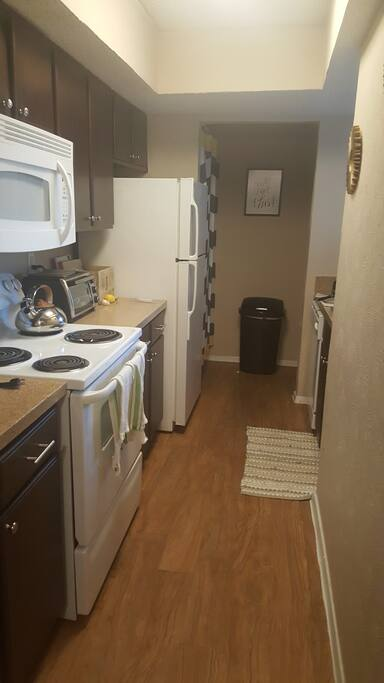 Full kitchen including dishwasher, pots & pans, cooking utensils, cutlery, and cleaning supplies.