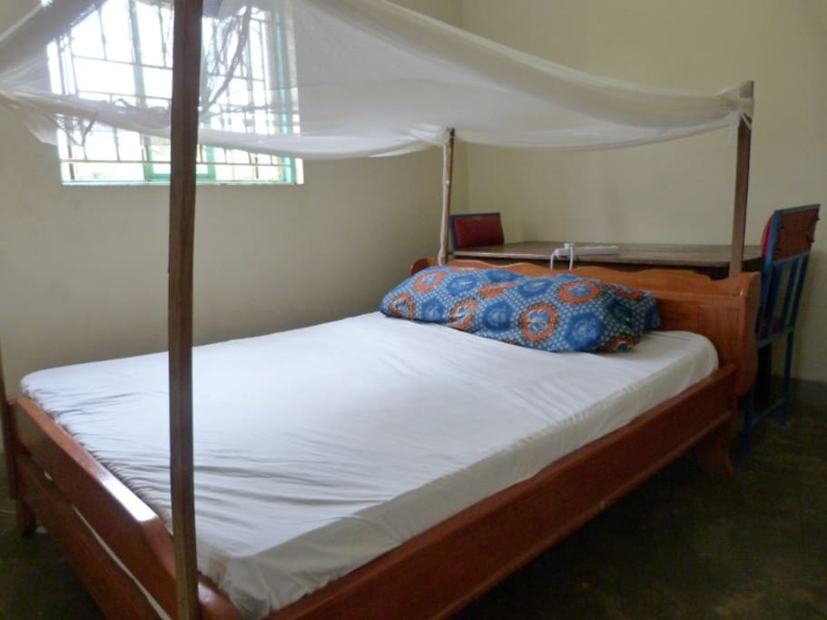 Bed with office desk behind it (mosquito net above).