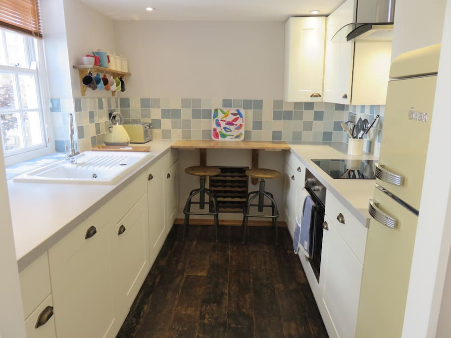 Fully fitted kitchen with breakfast bar & two stools.