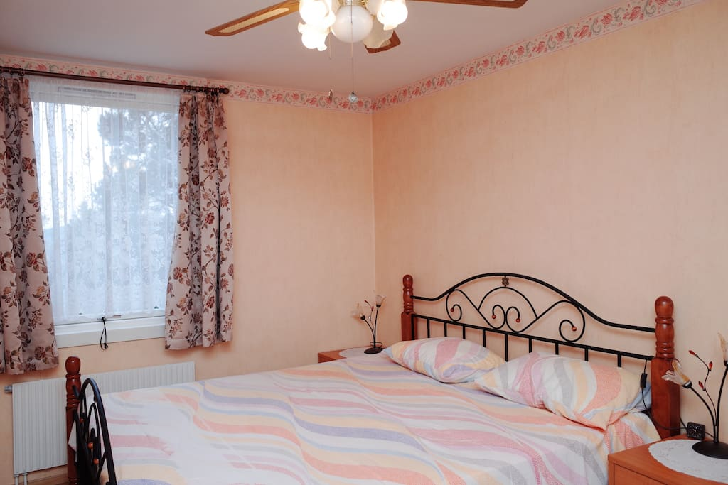 Your bedroom with a queen bed, ceiling fan and desk.
