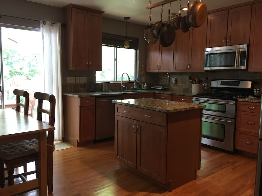 Eat-in kitchen with extendable table, granite countertops, and stainless steel appliances. Sliding glass doors access the deck and backyard.