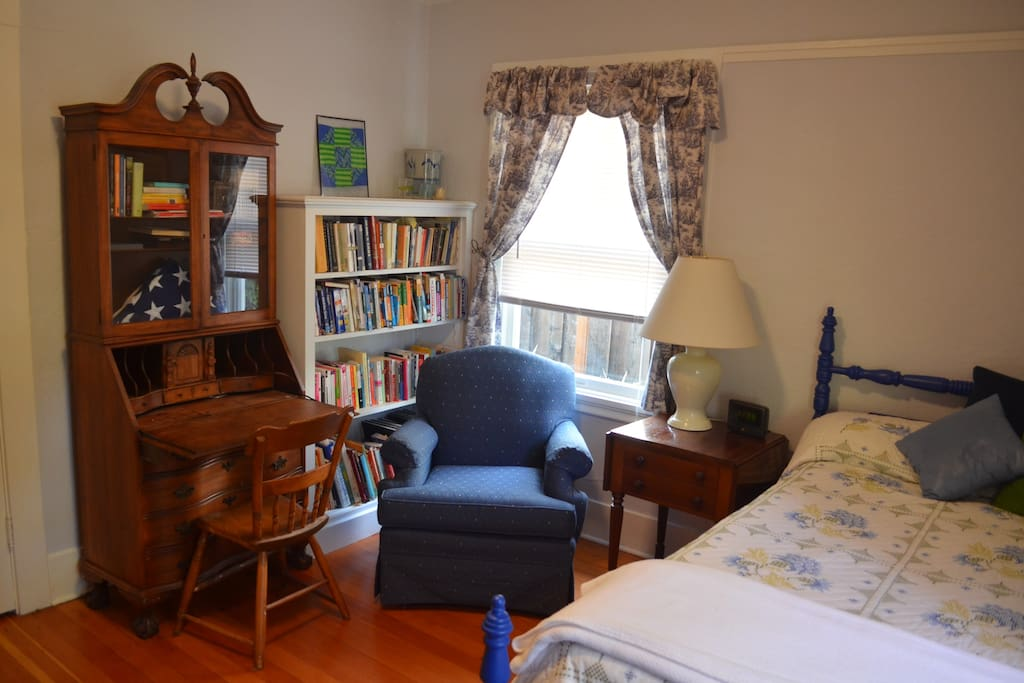 bedroom: twin bed, comfy chair, desk that can fold up to close.