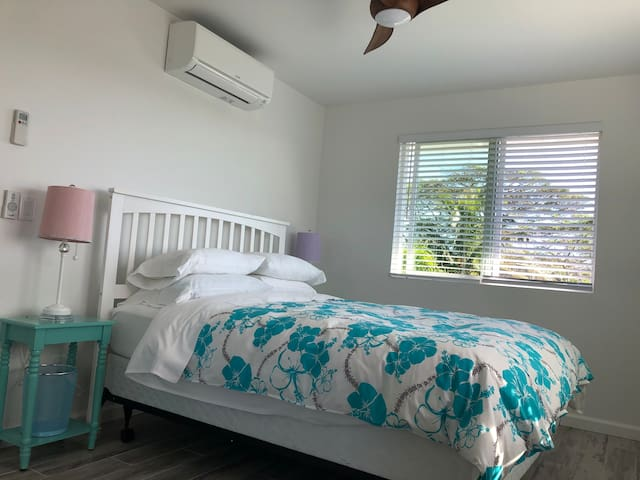 A queen size bed in a first bedroom. A/C and celling fan in the room make guests stay comfortably.