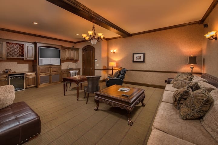 Gentlemens lounge with game table, wet bar, TV, dvd, and large sofa for relaxing evenings.