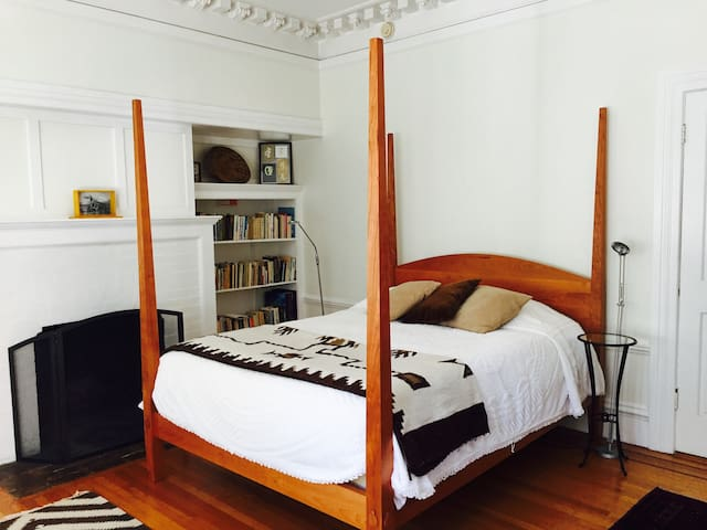 This is the handmade bed with fireplace by bookshelves.