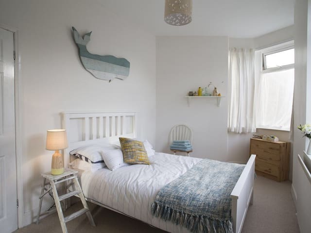 A bright main bedroom with a beachy vibe.