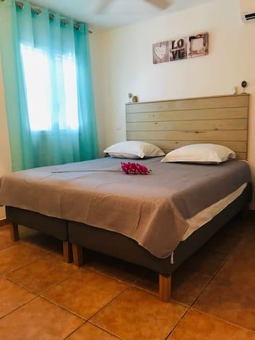 Belle chambre lit double King size (180x200) ou possibilité d'adapter en lits simples (90 x 200) pour 2 personnes célibataires, volets et moustiquaires aux fenêtres. Commode et placard mural avec coffre fort.