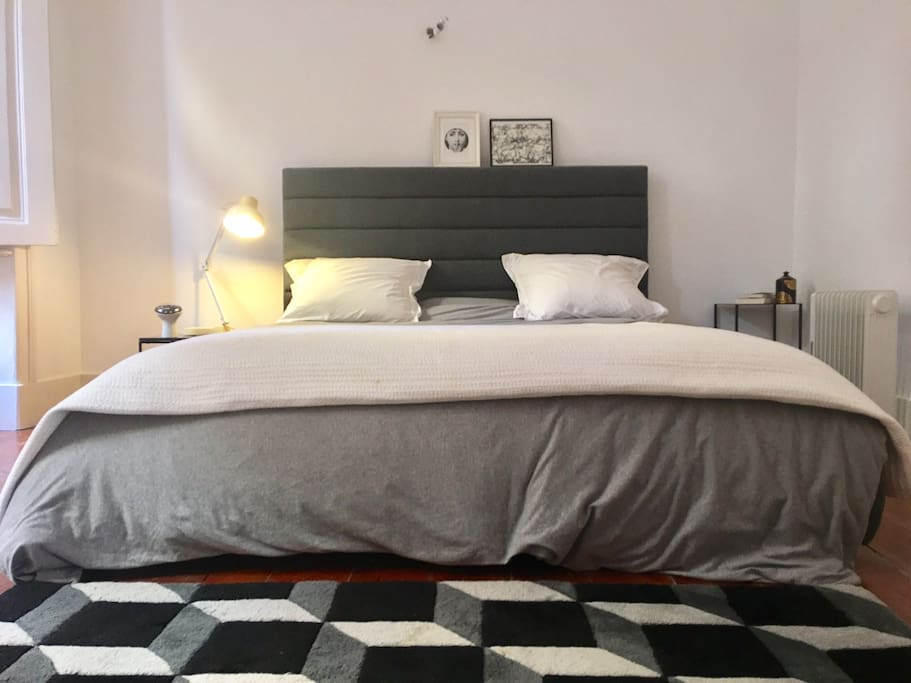 A large bedroom with a queen size bed