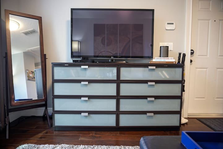Large screen TV with 4K Apple TV, a Blu-Ray/DVD Player, and movies stocked in the top drawers for your viewing pleasure.