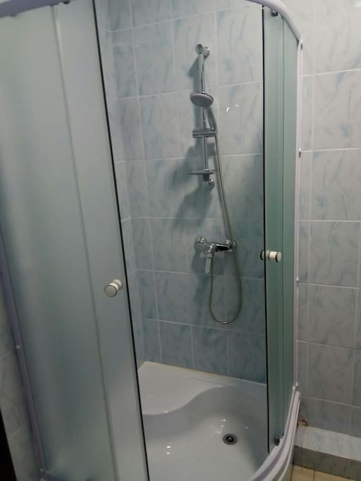 Room with double bed, shower, closet, drawers and toilet. Комната с двуспальной кроватью, душевой кабиной, шкафом, ящиками и туалетом.