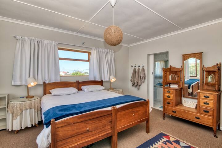 The main bedroom upstairs has a king size bed. It is made of two single bases, but has a King size mattress. There is a lovely view of the bay to be enjoyed and it is en-suite. The Bedroom has access to the veranda.