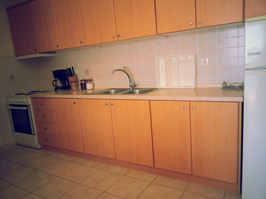 Kitchen with cooker and large fridge freezer