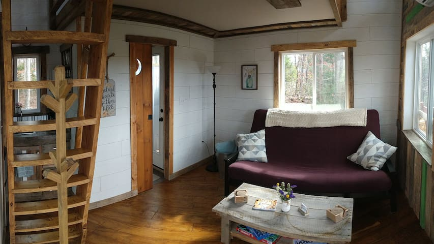 When you first walk into the treehouse you are welcomed with a rustic, yet sophisticated custom designed interior living space showing everything from plywood hardwood floors, to a pallet wood coffee table, to a large sofa for during the day or a comfy queen size bed for the night.