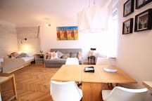 Sitting area, dinning area, double bed and tv.