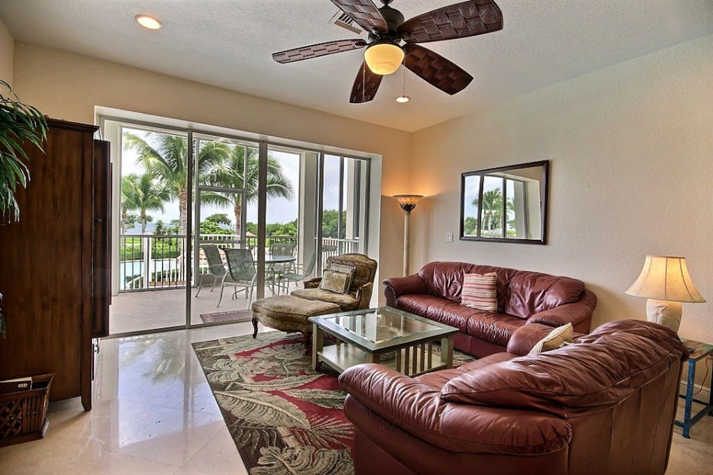 Living room and balcony overlooking the lagoon pool with views of the ocean.