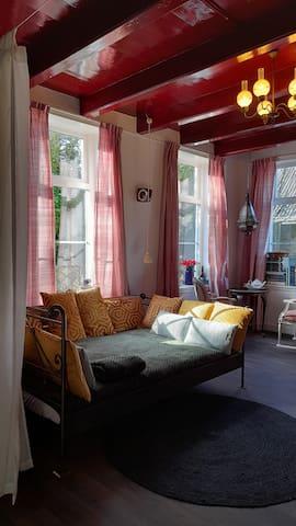 2e Woonkamer / Relax / Chillkamer, 2 persoonsbed cq loungebank met kussentjes, bedstee met stapelbed, Zitje met 2 stoelen, Pelletkachel, TV, Kunstboeken e.d. ,