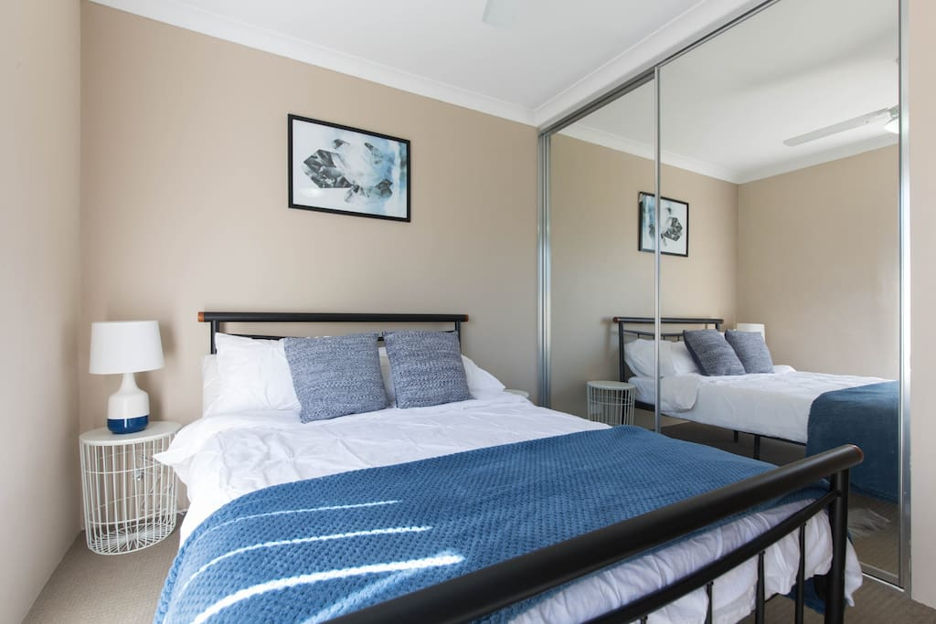 Comfy Double bed in a spacious room with cupboard space and ceiling fan.