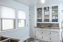 Open glass covered built-in kitchen cabinets with tons of storage. Coffee maker and Garbage can are stowed away in the tall pantry cabinet.
