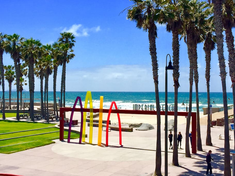 """Beautiful views of the beach, pier, and colorful """"Surfhenge"""" art from the living room, balcony and Master Bedroom."""