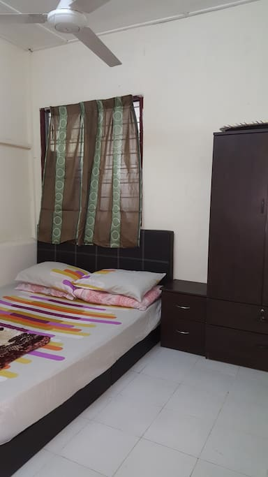 The srcond bedroom with queen bed, side-table and cupboard