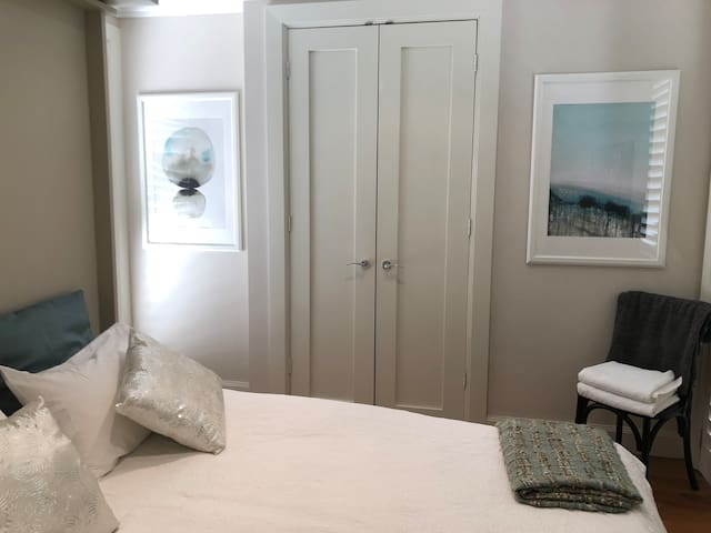 Your room with ensuite.  Luxury finishes, timber floor boards and doors opening to the garden and pond courtyard with water feature.