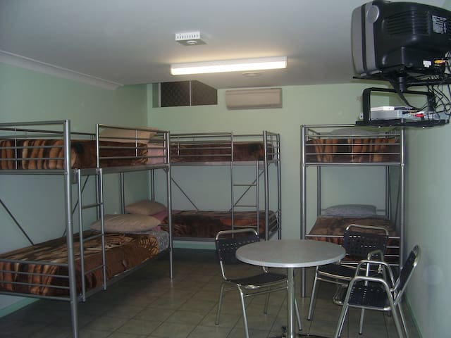 Bunk Style beds (6) with TV, Table chairs. Air conditioning unit.