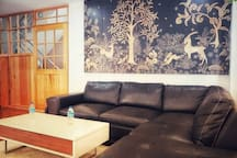 Living room with large comfy genuine leather sofa/recliner set. The centre table can be converted into a work desk