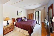 Find quiet privacy in the master bedroom, furnished with a plush king-size bed.