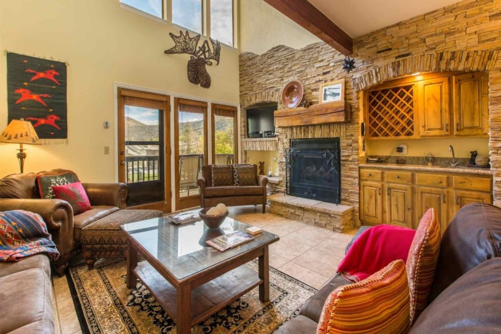 Stunning great room with a floor to ceiling wall of stone work with fireplace, large HDTV with Comcast TV and comfortable leather furnishings.