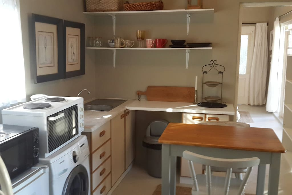 Kitchen area with stove, microwave and washing machine.