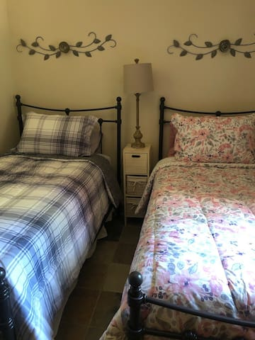 Twin beds in the basement bedroom. Large window can be opened to let in the cool air and light.
