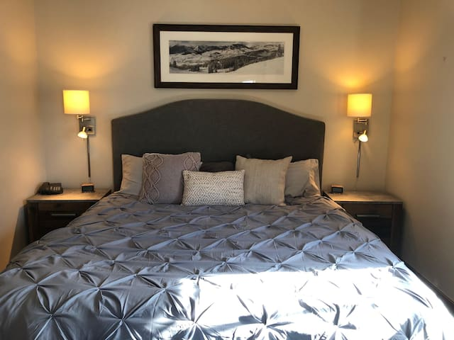 Cozy king bed in a room with gorgeous views and an en suite bath with deep soaking tub and rain shower.