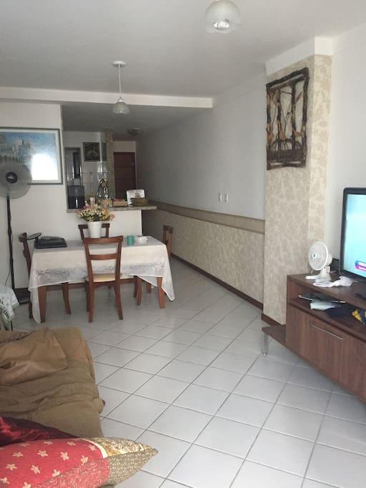 Sala com mesa e 4 cadeiras, 1 sofá-cama, televisão de 40 polegadas.
