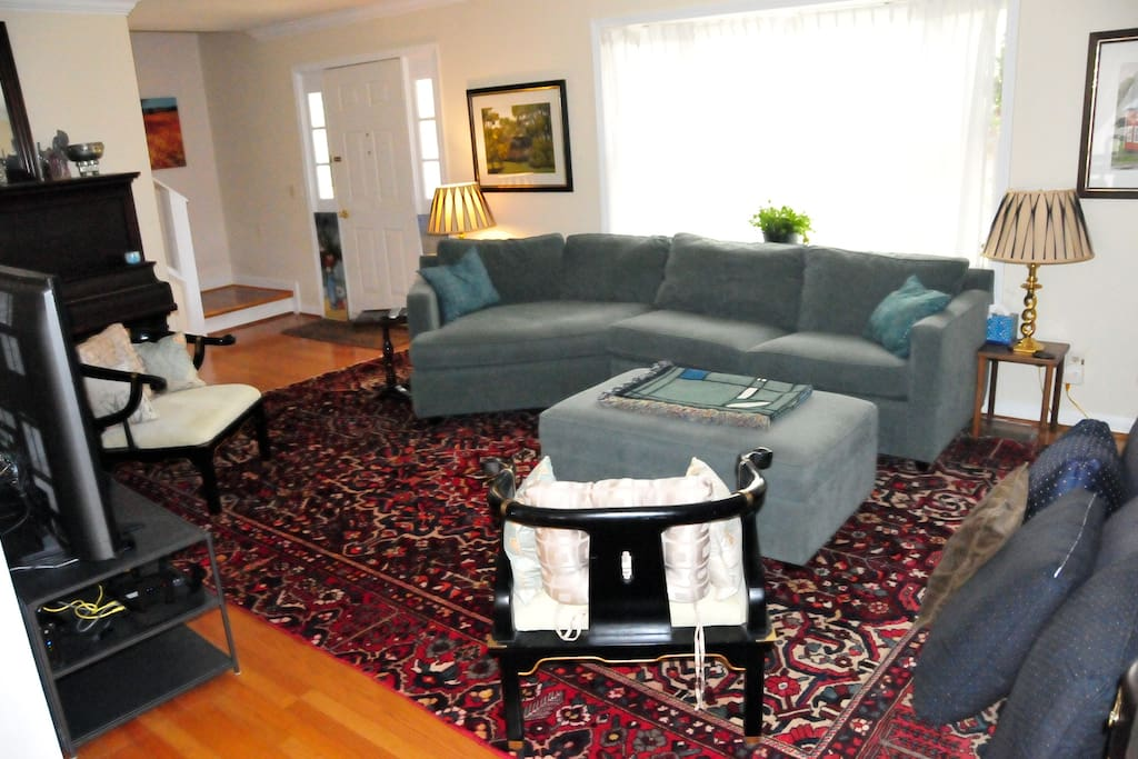 This comfy, open living room has a large TV, massive couch, and standing piano