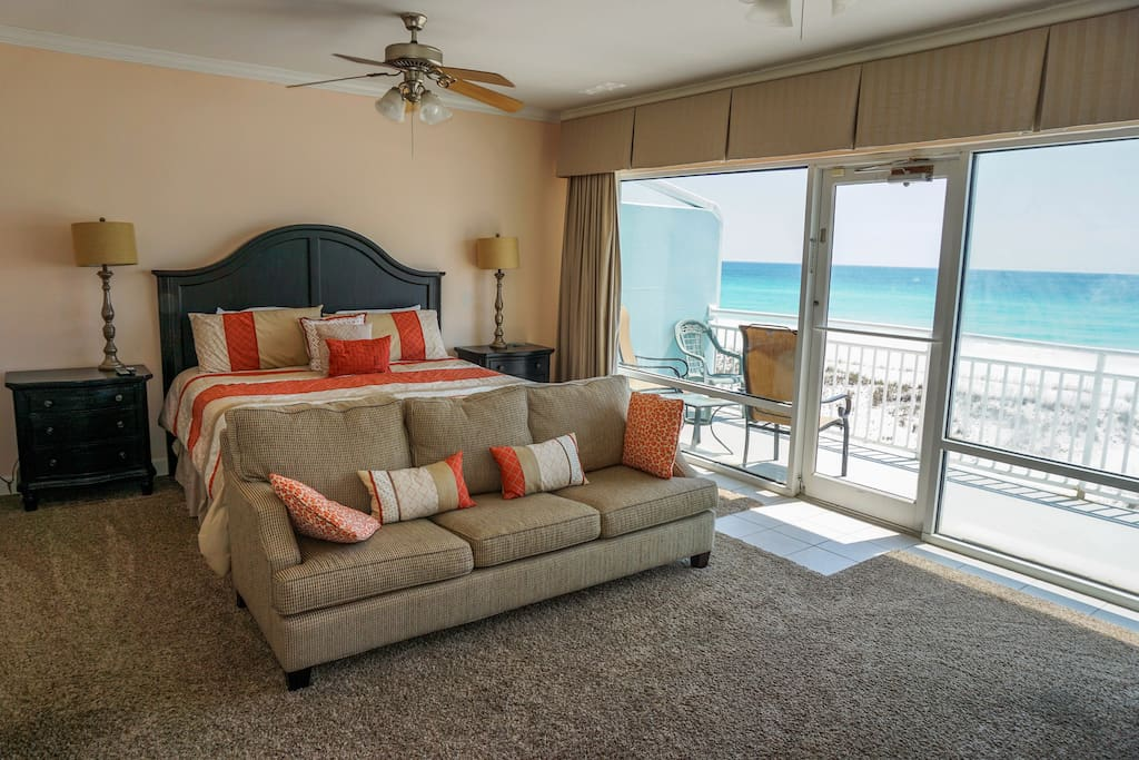 Master bedroom with king size bed and balcony overlooking sugar white sand beach and emerald waters