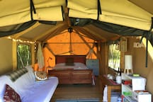 Beautiful Glamping tent on a deck and solid wooden floor with natural timber framing.  Queen bed and pull out futon double bed. Internal area 3 m by 5 m with a 2 m covered verandah