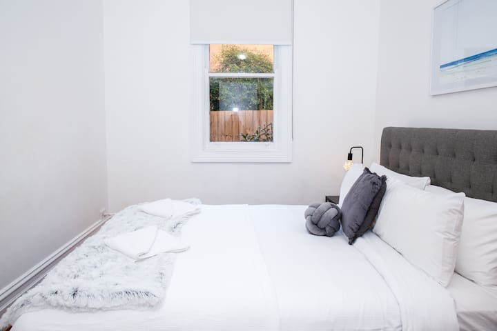 Natural light streams through the bedroom window creating a seamless connection with the world outdoors.