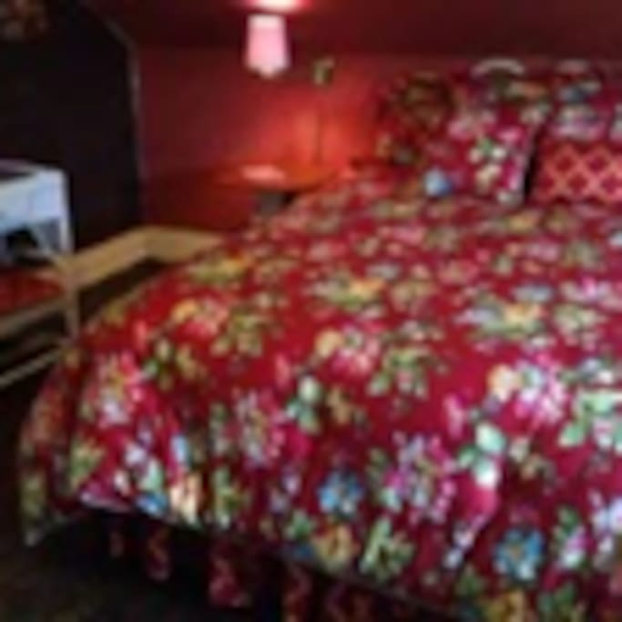 Red bedroom is cozy and private with its own footed tub and commode cubicle; lavatory and wicker furnishings as well as cornices from old house that burned that are made into bedside tables by local craftsman.