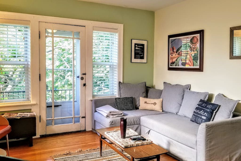 """Living Room. One guest reported, """"There is a welcoming front living room with a small balcony that looks out over the street. We enjoyed Netflix on the couch.""""  :)  We change some of our decor and furnishings seasonally, but we always keep this same layout."""