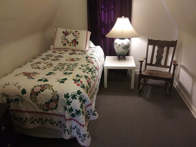 Charming little bedroom hosts trundle bed, bedside table, chair and small dresser.