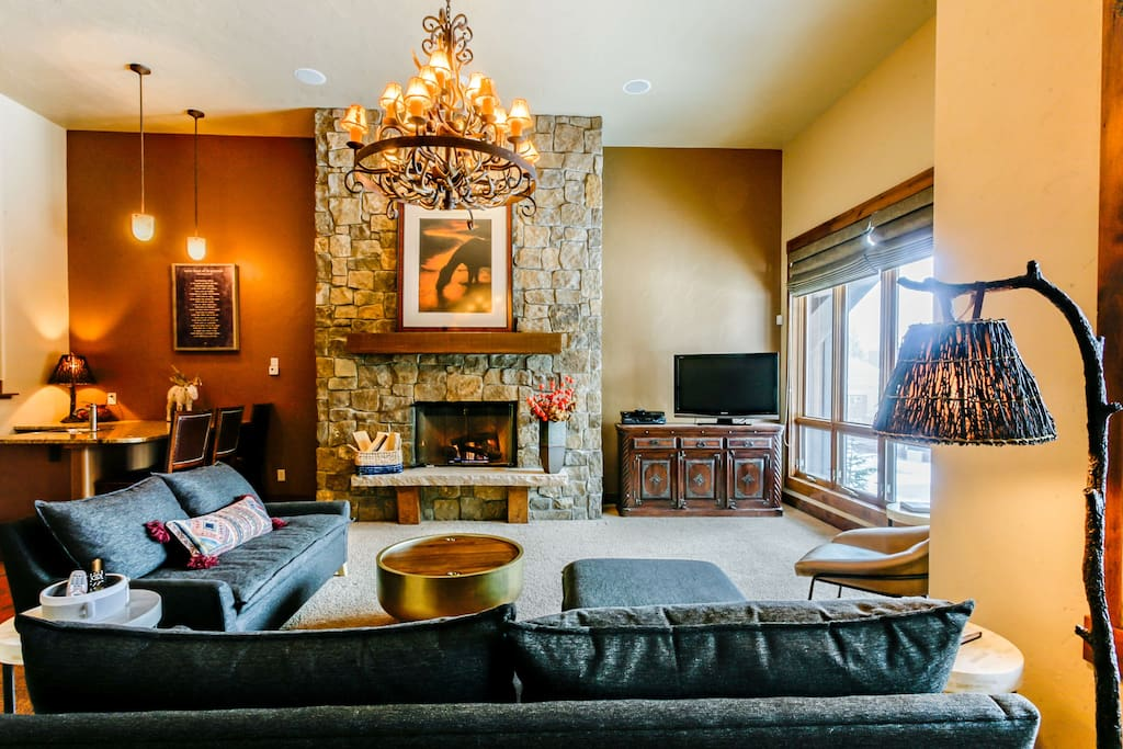 Main level lounge with fireplace, flatscreen TV and large sectional couch.