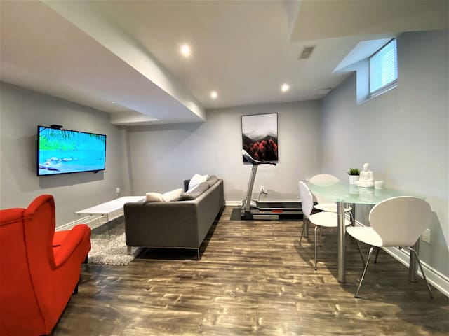 Living and Dinning area. 55 Inch TV with Roku and 1000+ TV channels. Netflix, YouTube, Amazon Prime, casting. Treadmill for fitness needs. Comfortable and elegant couch. Comfy Wingback chair with foot stool. Elegant centre table.