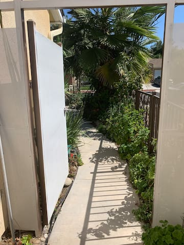 Path to the front yard through a security gate with keyed lock.