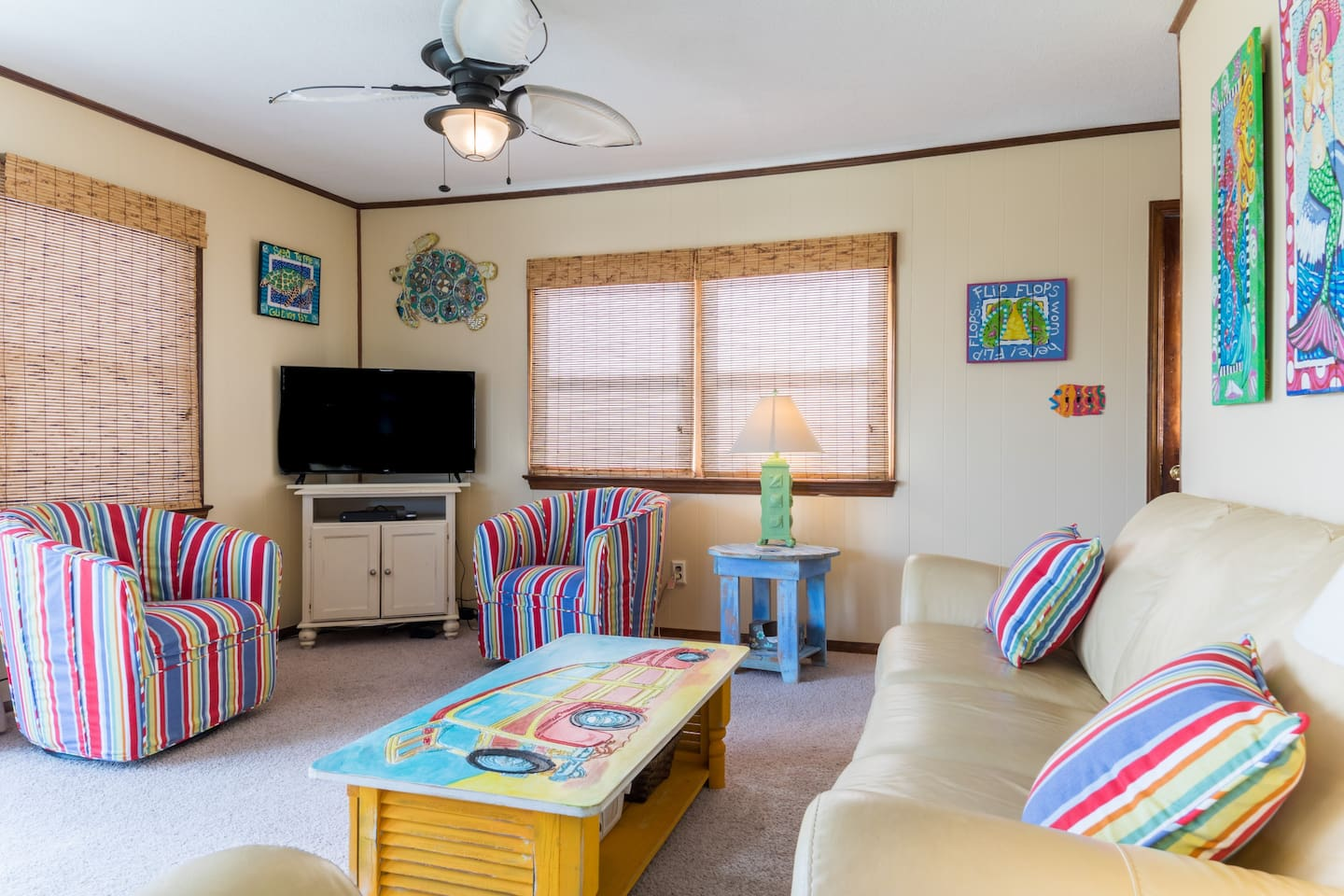 Living room with smart TV and ceiling fan, located on middle level with access to outdoor porch facing ocean!